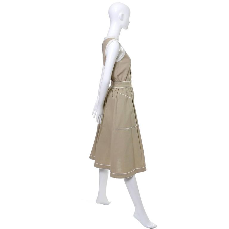 This 2 piece vintage Valentino linen dress is in as new condition and was made in France in the 1970's. The outfit has a scoop neck top that buttons up the front and a pretty skirt with pockets that buttons on the side. The taupe linen is piped in