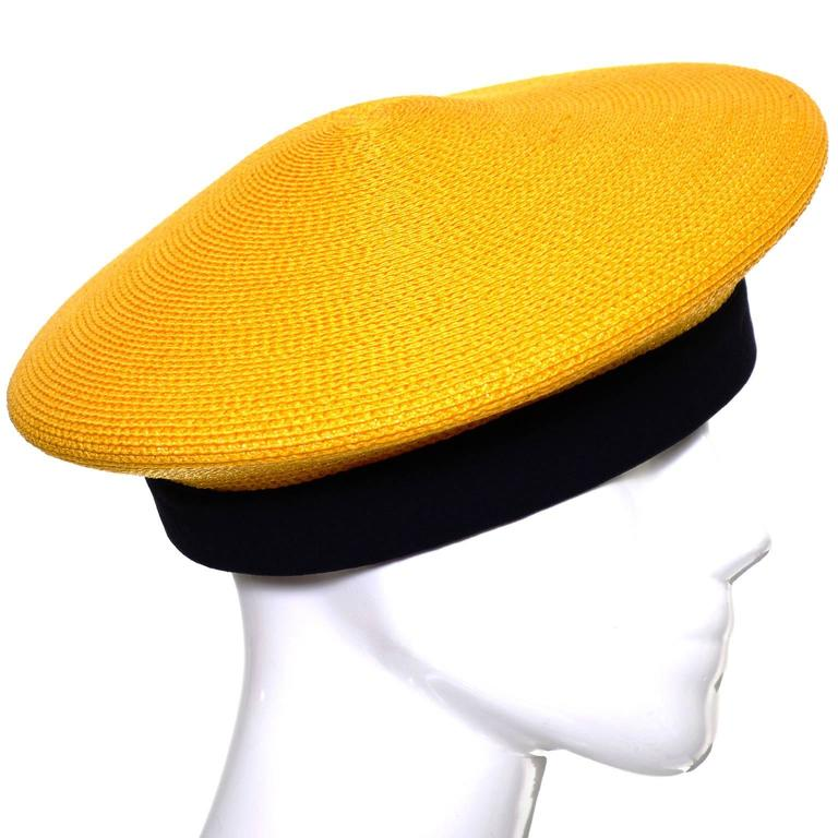 This pretty vintage Donna Karan marigold yellow straw beret has a black silk band and appears to have never been worn! The hat measures 21 and 1/2 inches on the inside in circumference.