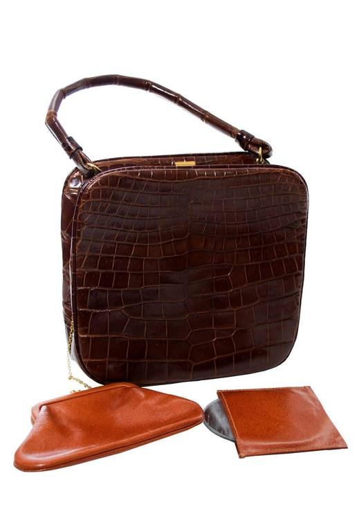 "You'll love this beautiful 1950's genuine alligator Koret vintage handbag with original coin purse and mirror. This bag closes at the top with a gold clasp and has a 12"" handle.  There are 2 inside pockets and the handbag measure 6 inches high and 6"