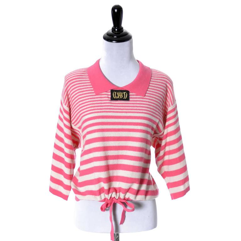 This 1980's Pink vintage 2 piece sweater set was designed by Sonia Rykiel and made in Italy.  The cream and pink wool drawstring striped top has a solid pink oversized sweater with logo buttons and fabric sash. The wonderful striped sweater top has