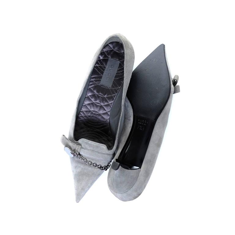 """These gray suede Gucci vintage shoes have never been worn. They have the Gucci medallion and chain detail, 1 and 3/4 inch kitten heels, and quilted satin insoles.  The shoes are a size 7 and 1/2 B and measure 3"""" on the outside at the widest part of"""
