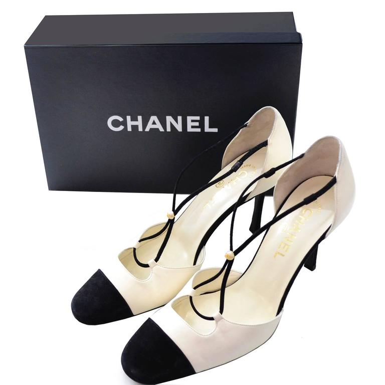 These are beautiful Chanel shoes in ivory leather and black suede.  The pretty black suede cross over straps have small pearls with the Chanel logo.  The shoes are in their original box and come with a Chanel logo plastic zip bag with extra heel