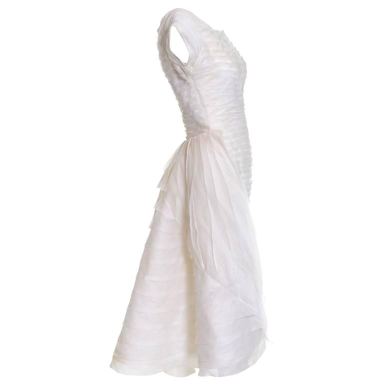 This is an absolutely outstanding vintage dress from William Cahill of Beverly Hills.  I have sold several Cahill vintage wedding dresses over the years and this one is one of my favorites!  The simple ivory organza wiggle dress is pleated and has a