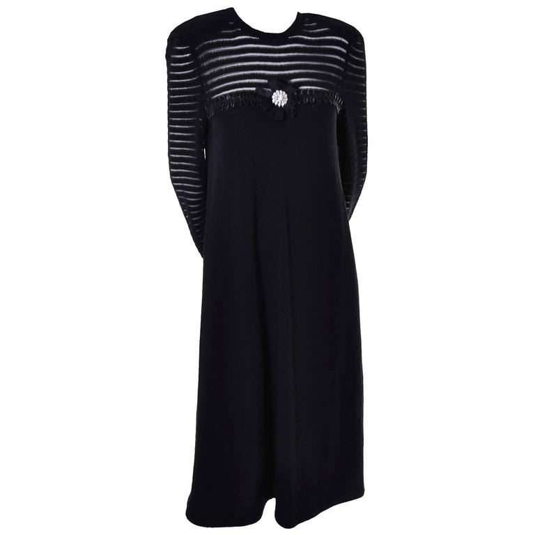 This 1970's Adolfo Vintage black knit dress is loose fitting and has satin trim and a bow with a giant rhinestone button on the bodice.  The sleeves and upper part of the bodice are woven so that they look almost like stripes, revealing just