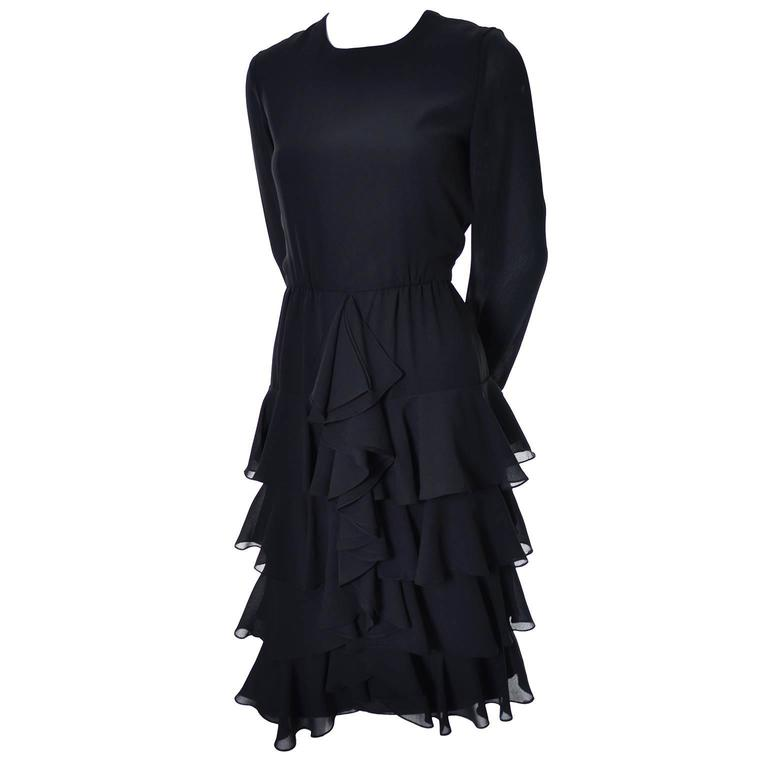 This is a great vintage dress from designer Bill Blass. The dress is layered with ruffled black chiffon crepe and it zips up the back. The long sleeves have ruffled cuffs and though the content label has been removed, the dress has the Bill Blass