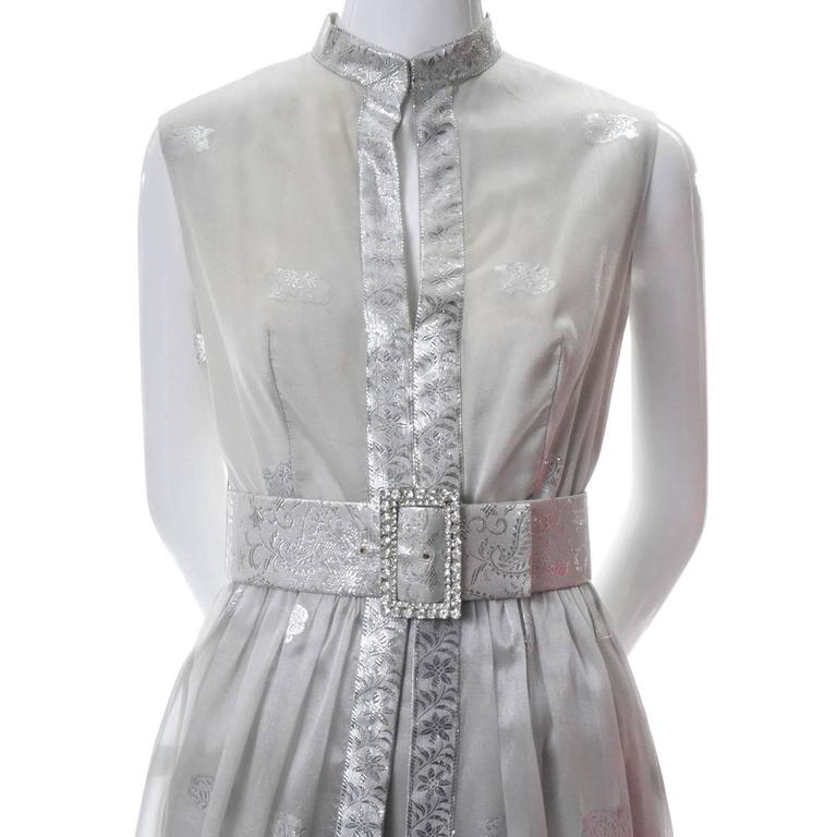 This stunning evening outfit was designed by Oscar de la Renta in the 1970s.  This amazing outfit has a metallic embroidered organza sleeveless dress over a pair of built in pants.  The dress comes with its original belt that has a beautiful