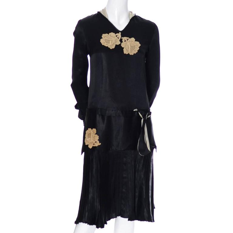 This lovely vintage black silk 1920's dress has a pretty collar that has panels that drape down the back, a pleated drop waist skirt and rose lace applique.  The ruffled cuffs are so beautiful and the cuffs, collar and panels are lined in ivory