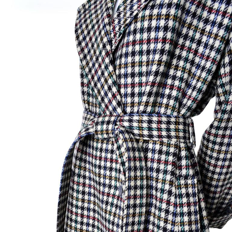 This fabulous vintage coat was designed by Kenzo in the 1980's.  The coat is 100% wool in a modern black, white, red, gold and green houndstooth plaid. The coat has pockets, a fabric belt, and is fully lined in a 70% wool 30% nylon blend. There are