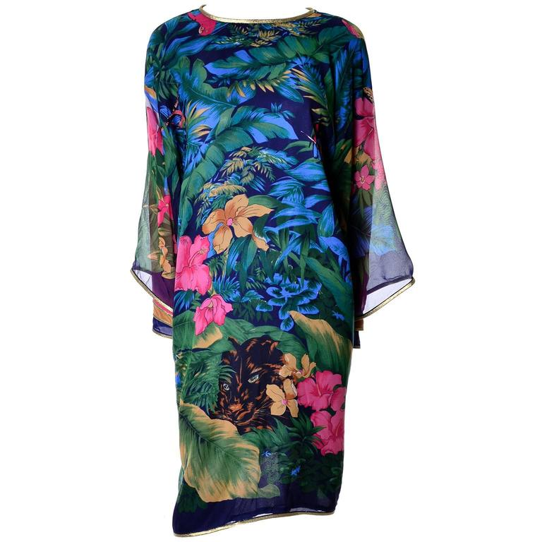 This is an outstanding vintage caftan style dress in a beautiful silk chiffon floral print with navy blue lining.  The dress ties at the back of the neck with gold ties that have jeweled tassels on the ends and the back is somewhat open to the