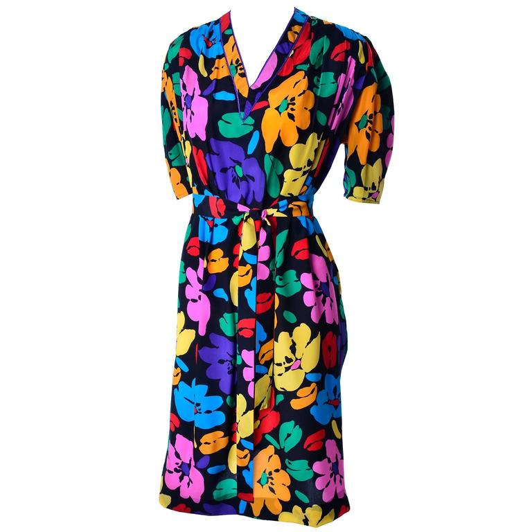 This Emaunel Ungaro Parallele dress is in a wonderful bright floral silk print. The dress fits very loosely and can be worn with or without its fabric tie. The beautiful floral print has shades of purple, red, blue, yellow and orange flowers that