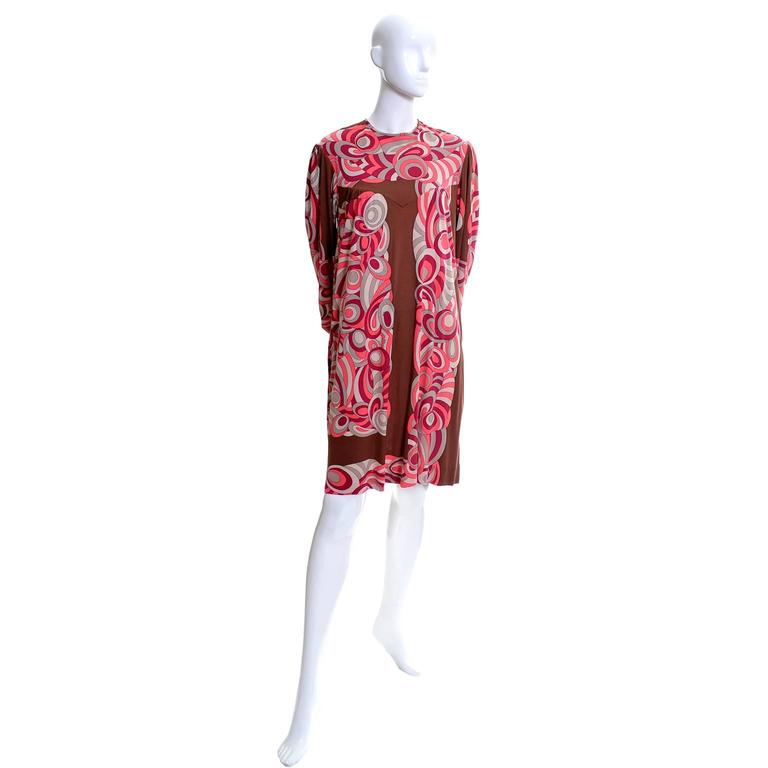 This vintage silk jersey Pucci dress came from the estate of a woman who knew Emilio Pucci and often visited him at his home in Italy.  The dress is brown with a mod raspberry, coral and gray design.  The dress is labeled a vintage size 10 and fits