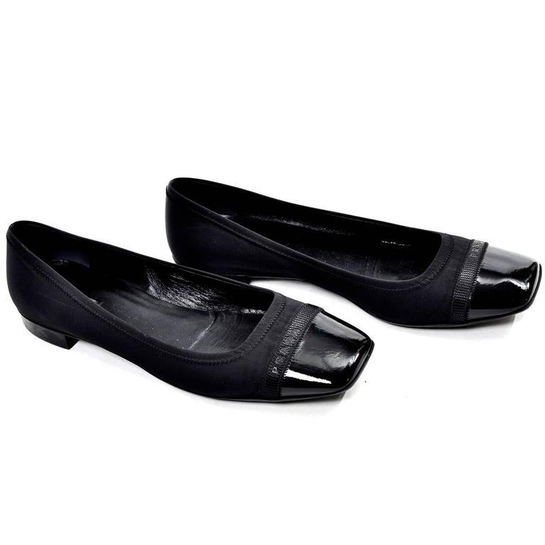 "These are classic black Prada flats with a leather-lined fabric upper and a patent leather toe. There is a black ribbon across the toe with ""Prada"" in black. Made in Italy. They look never worn and are in excellent condition. No marked size, but fit"