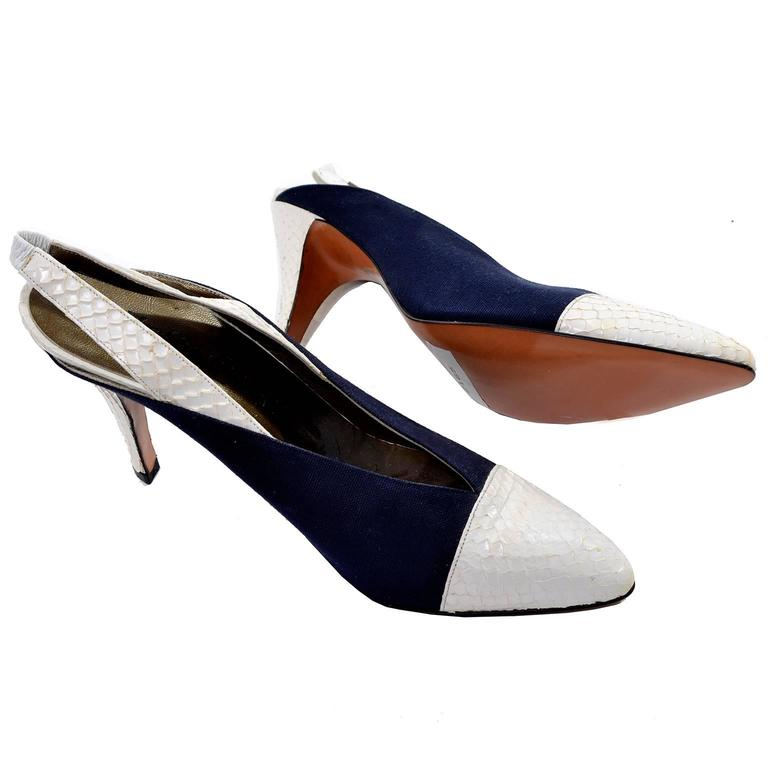Beautiful Yves Saint Laurent vintage heels with white snakeskin toe, heel, and strap. Slingback style with a pointed toe and navy sides. The slingback strap has a small piece of white elastic in the back for comfort and ease slipping into these