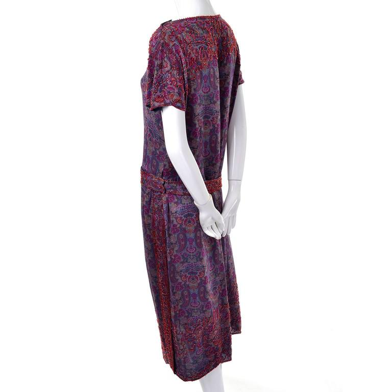 This extraordinary 1920's vintage dress is lightweight wool in blue with a magenta, green and yellow paisley print design. Small red glass beads decorate along the hem and carry on to the end of the sleeves from the bust. The sleeves and bottom hem