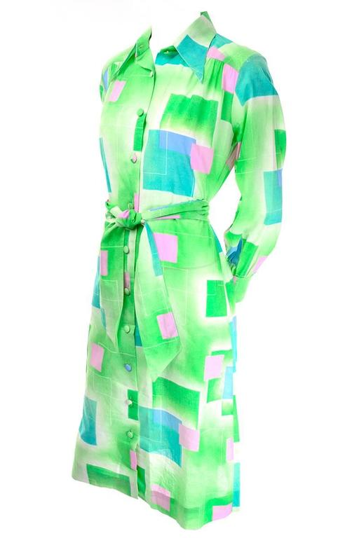 This vintage dress by Lanvin is from the 1970's and the fabric is covered in Green, pink and blue abstract squares.  The dress buttons up the front and has long sleeves with buttoned cuffs.  This dress comes with its original fabric belt and fits a