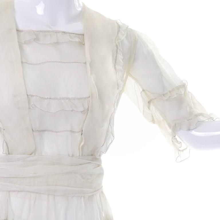 This is a beautiful off white vintage Edwardian organdy dress with ruffles and a sash. The dress has three quarter length sleeves , a snap in front panel and is sheer. We estimate this would fit size 4/6. This dress would make a wonderful wedding