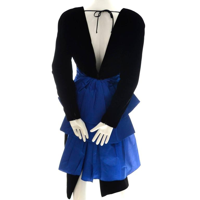 This pretty 1980's vintage A. J. Bari dress is made of a beautiful silk and rayon black velvet fabric and accented with blue taffeta at the waist. There are shoulder pads and the back of the dress ties at the neck and is open to the waist. There is