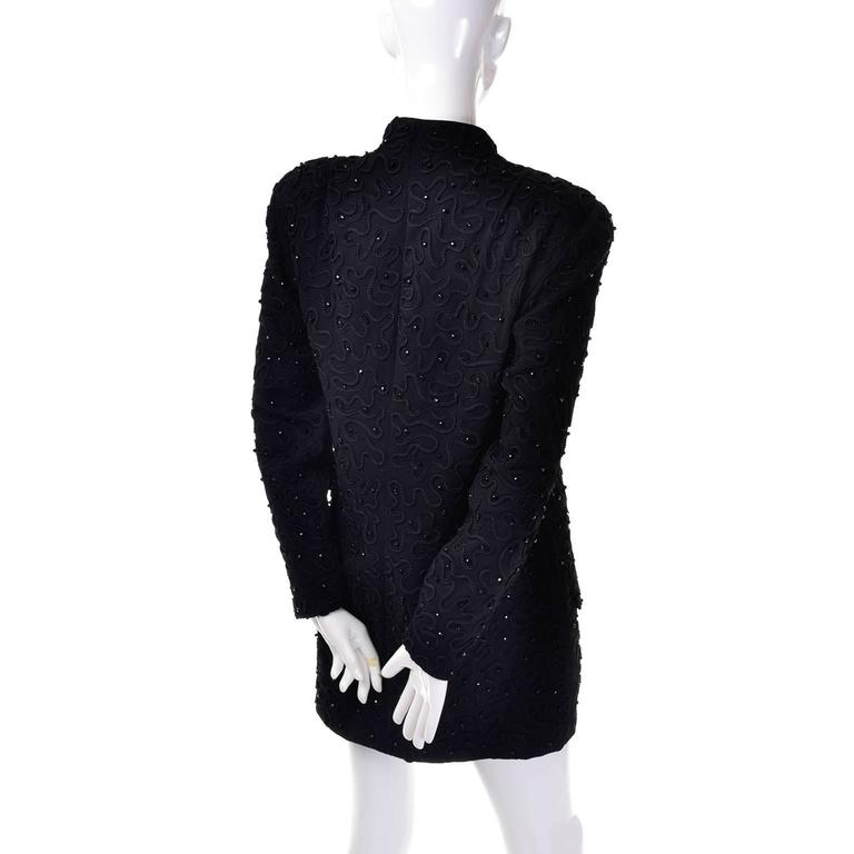 This is a gorgeous 1980's black Donna Karan New York Wool Blazer Jacket with beading and swirl raised embroidered design. Decorative buttons run down the front of this jacket, with hidden snap closures underneath. There are shoulder pads and long