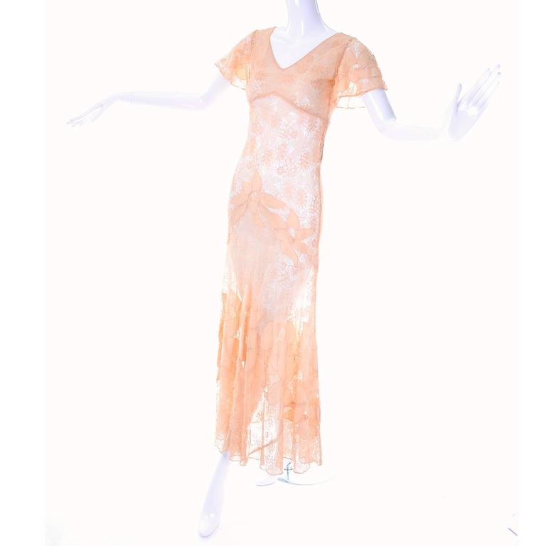 This gorgeous peach lace vintage 1930's dress has beautiful floral appliqués. This long gown has an empire waist, but is form-fitting, with a fishtail skirt and butterfly sleeves. Fits a modern size 2/4 but please review the measurements carefully