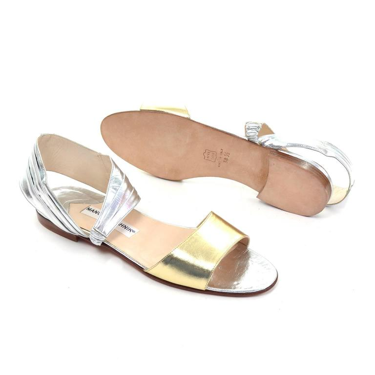 These vintage Manolo Blahnik London sandals were never worn! These fabulous shoes have a gold toe strap and a silver ankle strap, that is connected at the outer arch with an elastic piece and is pleated across the top and along the outer side of the