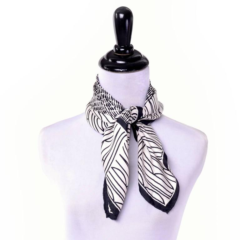 This 1980s square silk scarf by Bill Blass is black and white with his logo name in thick, uppercase letters repeated in a thick band along the edges. The center square has rows of abstract calligraphic dashes. This scarf has a hand rolled edge and