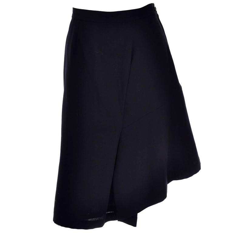 This is a fabulous avant garde Comme des Garcons skirt that hits just below the knees, with an asymmetrical hemline created by interesting gathering, diagonal seams, draping and pleats created across the skirt in the front and back. This midnight