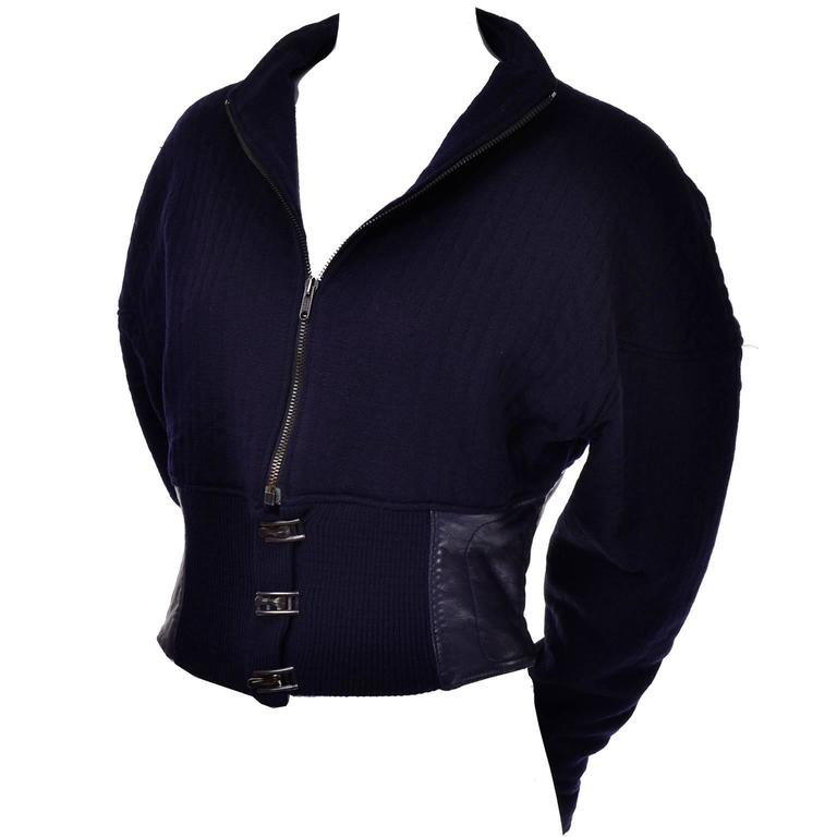 This is a wonderful Claude Montana vintage 1980's cropped jacket made of deep navy blue knit wool, with a navy blue leather waistband. This oversized jacket has drop shoulders, and 3 adjustable metal toggles at the waist. It zips up the neck, but