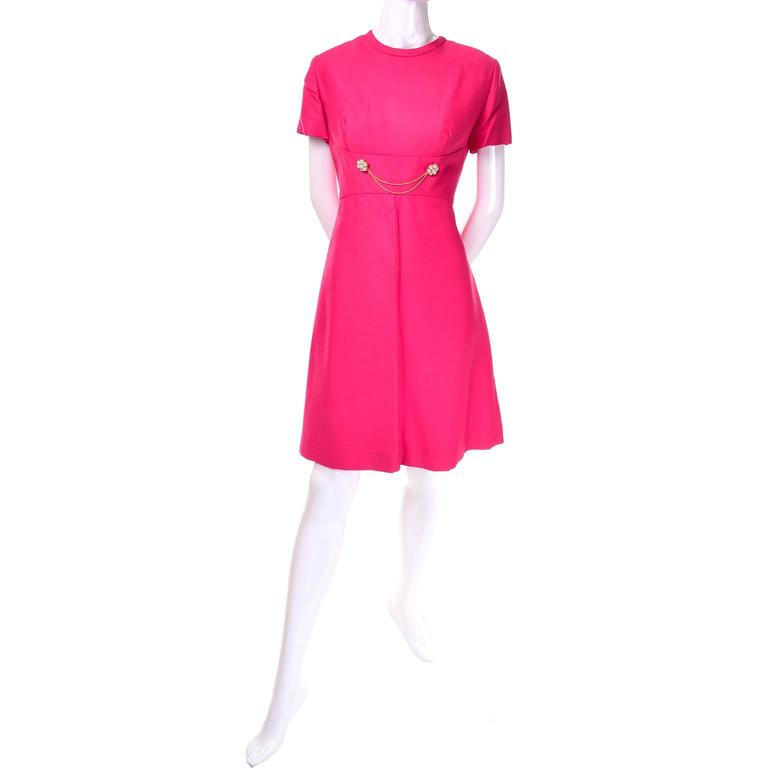 This bright pink dress and matching coat by Emma Domb is from the late 1960's but appears to have been barely if ever worn. The short sleeved dress has a fitted waist adorned with two chains and clusters of pearl beads. The coat has decorative