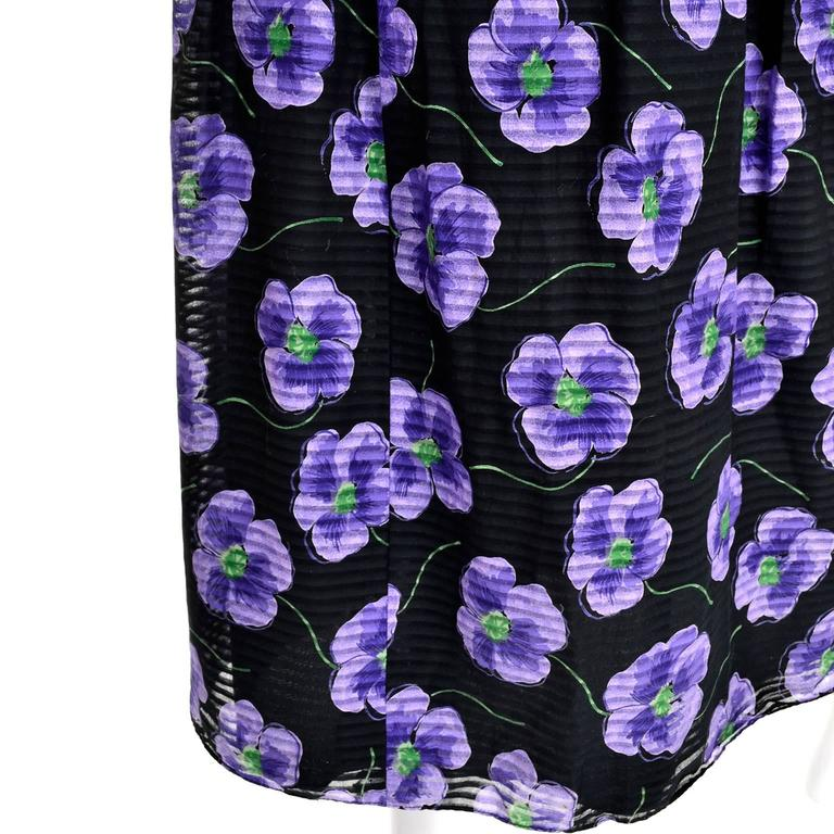 This is a pretty black Anthony Muto vintage dress adorned with beautiful purple flowers. The summer cotton or cotton blend voile dress has a sheer, subtly striped outer layer, and is lined in black fabric. It is sleeveless with a scoop neck and