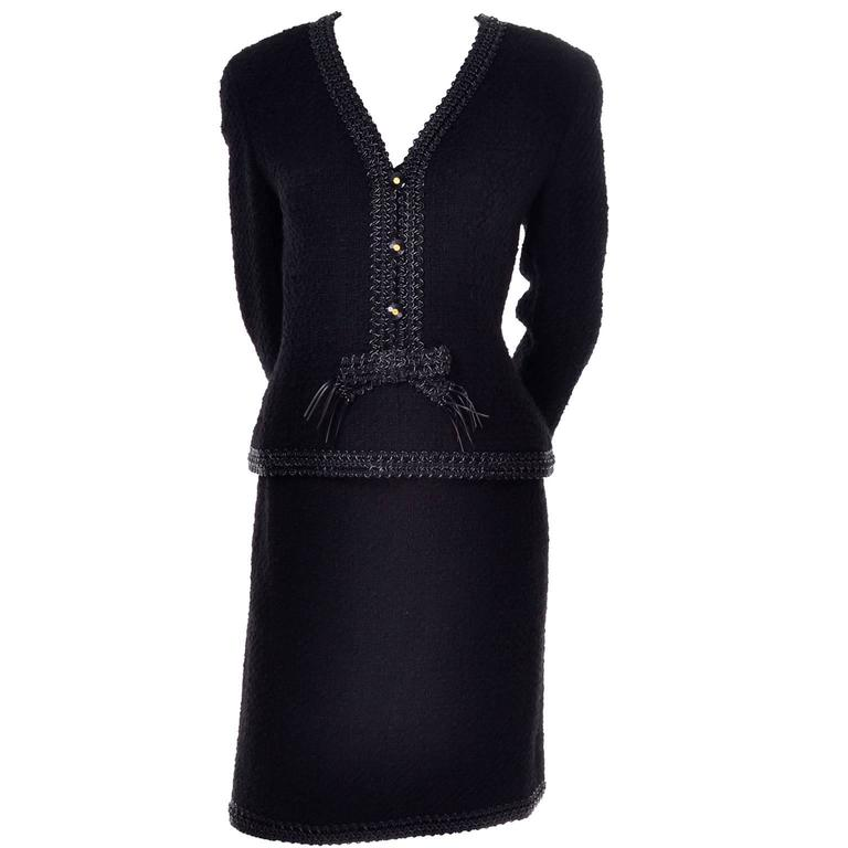 This beautiful black wool boucle Chanel suit is from Fall Winter 1994. The suit has a straight skirt and semi peplum style jacket. The jacket has decorative CC logo buttons up the front and closes with a back zipper. Both pieces have beautiful black