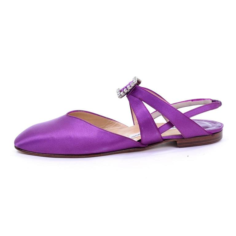These gorgeous purple satin slip on shoes were designed by Manolo Blahnik London in the 1980's. These fabulous shoes have a large rhinestone faux buckle and an elastic ankle strap. The two side straps join under the buckle in elastic, making these