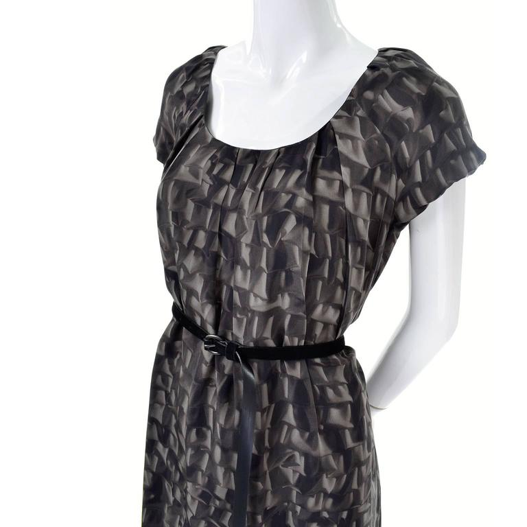This is a great Moschino Cheap and Chic silk dress with a unique abstract ruffle print. At first glance, you might not notice the pattern, but once worn, you can see the abstract pattern of the fabric!  This dress has a black suede belt that fits