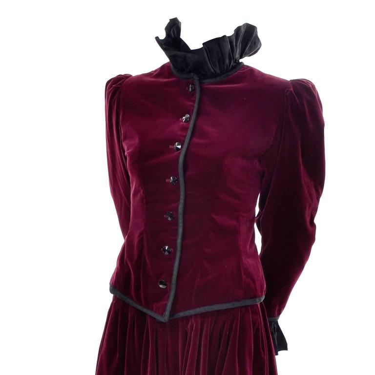 This incredible 2 piece evening ensemble is from Yves Saint Laurent and includes a jacket and a beautiful skirt both in luxe burgundy velvet.  The fitted jacket is fully lined, with ruffled black taffeta on the cuffs and collar. This beautiful high