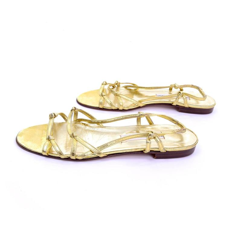 These summer slip-on sandals by Manolo Blahnik London have two knotted gold leather straps across the upper, and an ankle strap that is knotted on each side, with elastic on the back. These sandals have leather soles and have never been worn. They