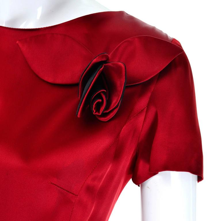 This is a great Moschino Cheap and Chic silky red and black vintage dress with 3d roses and a slight peplum. There is a zipper in the back at the waist and covered buttons on the top below the neck. The dress is approximately a modern day size 8/10