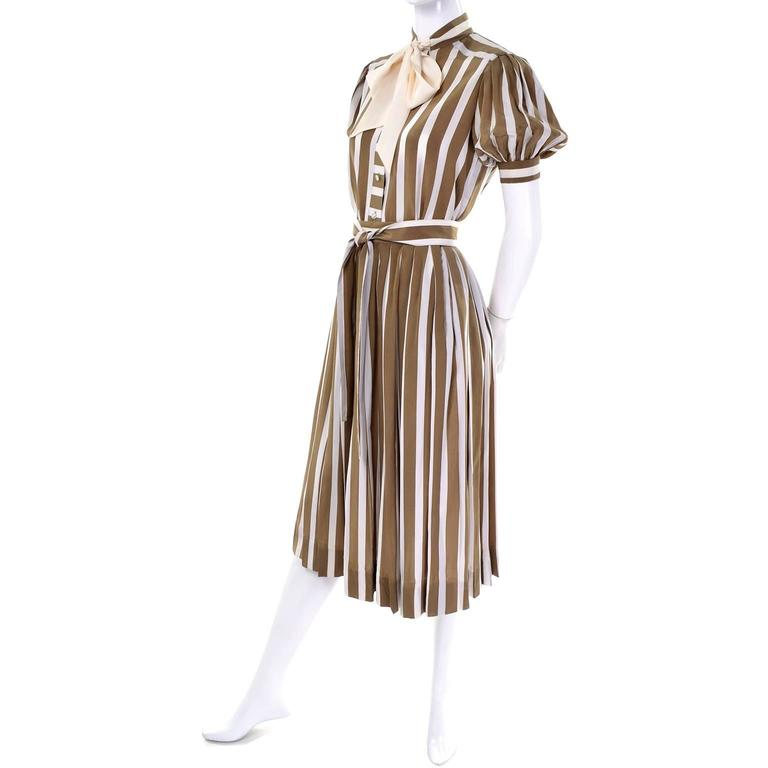 This pretty vintage 2 piece striped dijon mustard green and cream dress was designed by Albert Nipon in the 1970's. The dress includes a pleated skirt and a button front blouse with puffy short sleeves and a sash bow in cream. The skirt closes with