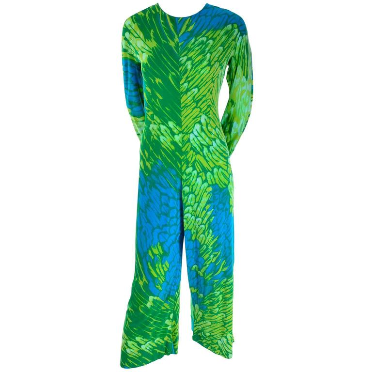 This vintage silk jersey jumpsuit is from the late 1960's or early 1970's and it comes with a matching sheer silk chiffon one shoulder sarong that slips over your head.  The jumpsuit has a great abstract blue and green print, it zips up the back and