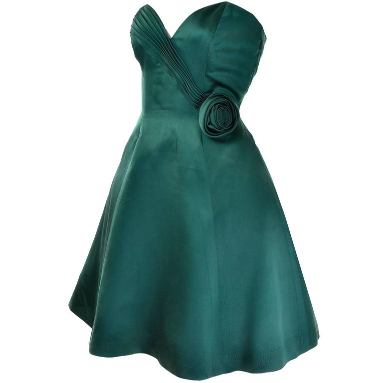 This vintage green evening dress was designed by Vicky Tiel and purchased at Bergdorf Goodman in the 1980's.  The dress is strapless and has a pretty pleated, heart shaped bodice, a rosette