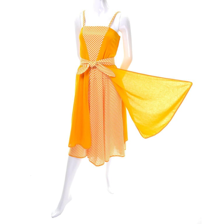 This bright and cheerful deadstock 1970's vintage sun dress by Lanvin has spaghetti straps and marigold orange/yellow and white strips on the skirt and in a V shape on the bust. The striped skirt is layered with four unique free-flowing panels that