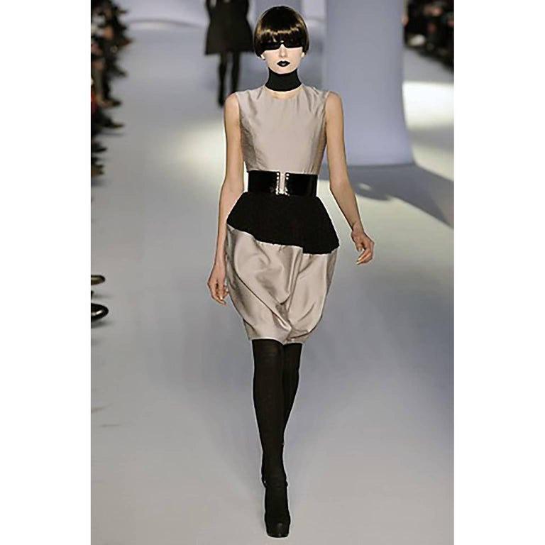 This YSL little black dress was designed by Stefano Pilati for Yves Saint Laurent for the Autumn Winter 2008 collection. The dress is shown in a two tone version with a belt in our photos from the runway show. This sleeveless black satin crepe dress