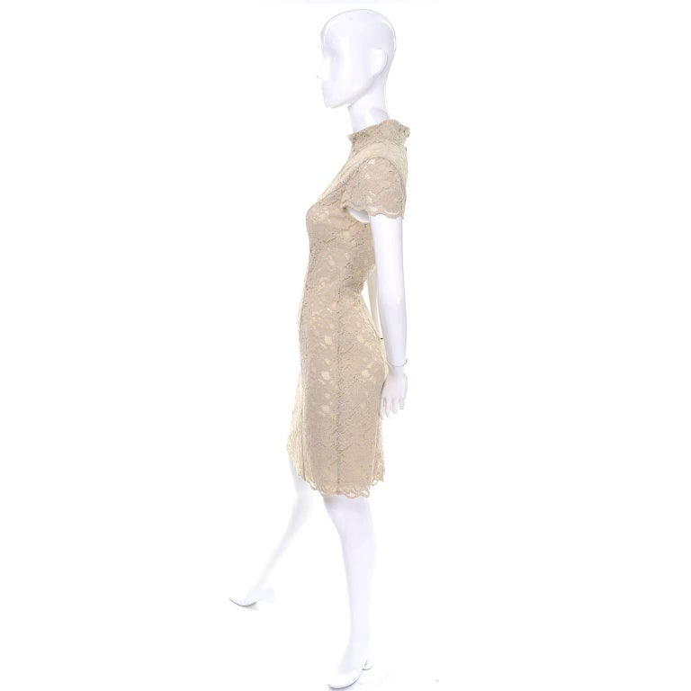 This is a lovely 1990's vintage Moschino Cheap and Chic floral lace dress that is lined in the body, with sheer cap sleeves. The edges are scalloped, and it closes with a zipper up the back and three hidden mother of pearl buttons on the raised boat