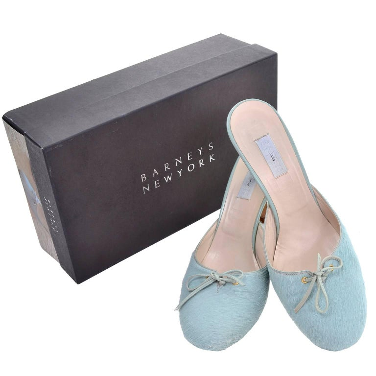 These Barney's New York blue pony fur backless mules or slides have leather trim heels and pretty leather bows. These shoes are labeled a size 37 and were made in Italy. These are 3.25