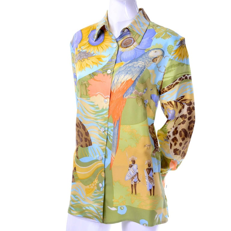 This is a beautiful vintage Ferragamo silk blouse in a tropical island novelty print that includes island natives, parrots, leopards, and gorgeous plants and flowers.  The blouse has long sleeves, buttons up the front and is labeled a US size 8.
