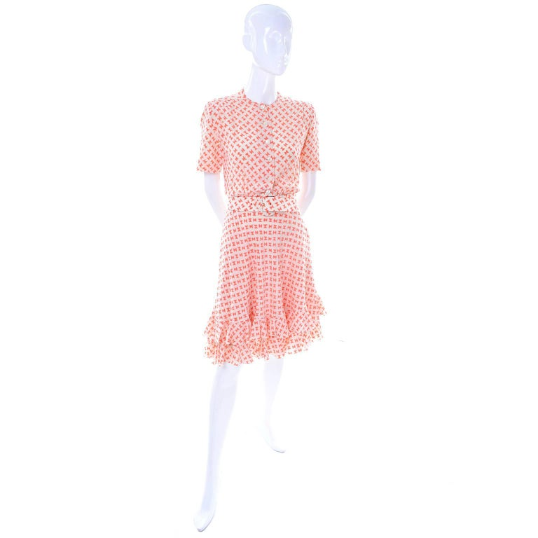 This couture vintage dress is in ivory silk with a fabulous orange bow print and it comes with its original fabric belt. There are moon glow type buttons up front and a side metal zipper. This perfect Spring or Summer  dress is lined and has a