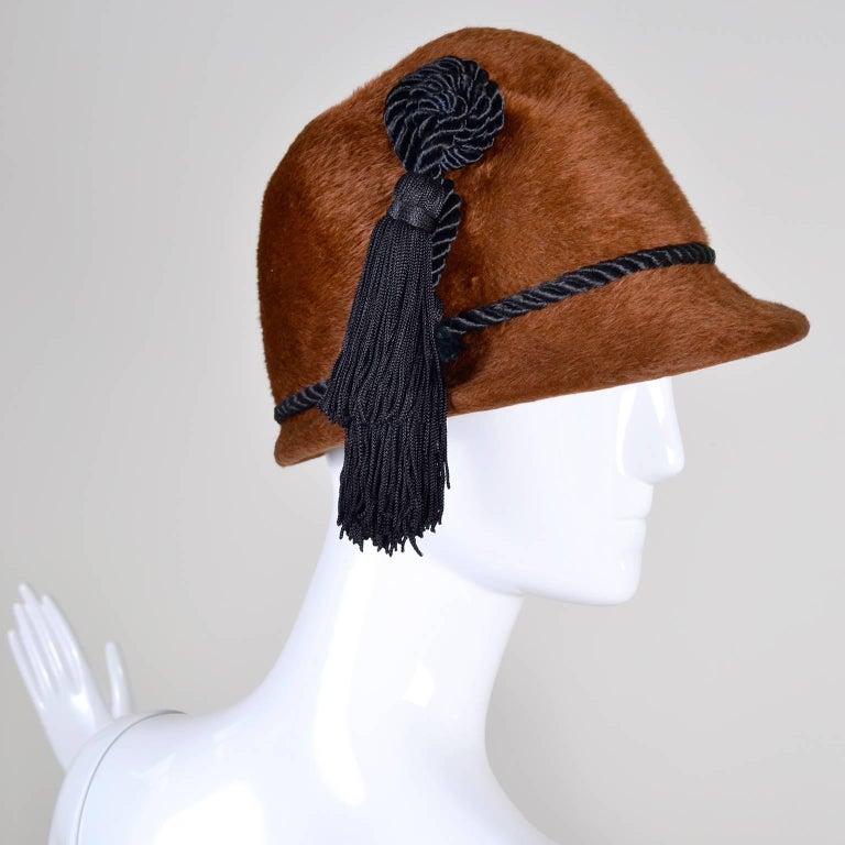 This is a luxurious brown faux fur vintage YSL hat with a short brim in front and a black braided cords There is a thin cord around the hat, and another black cord ending in two large black tassels that hang down past the brim. This hat is cloche