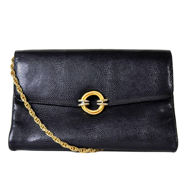 This vintage black handbag is from Rodo and was made in Italy in the 1980's. The bag is made in reptile embossed black leather and it has a beautiful gold double circle clasp that is embellished with rhinestones. There is a chain strap that can make