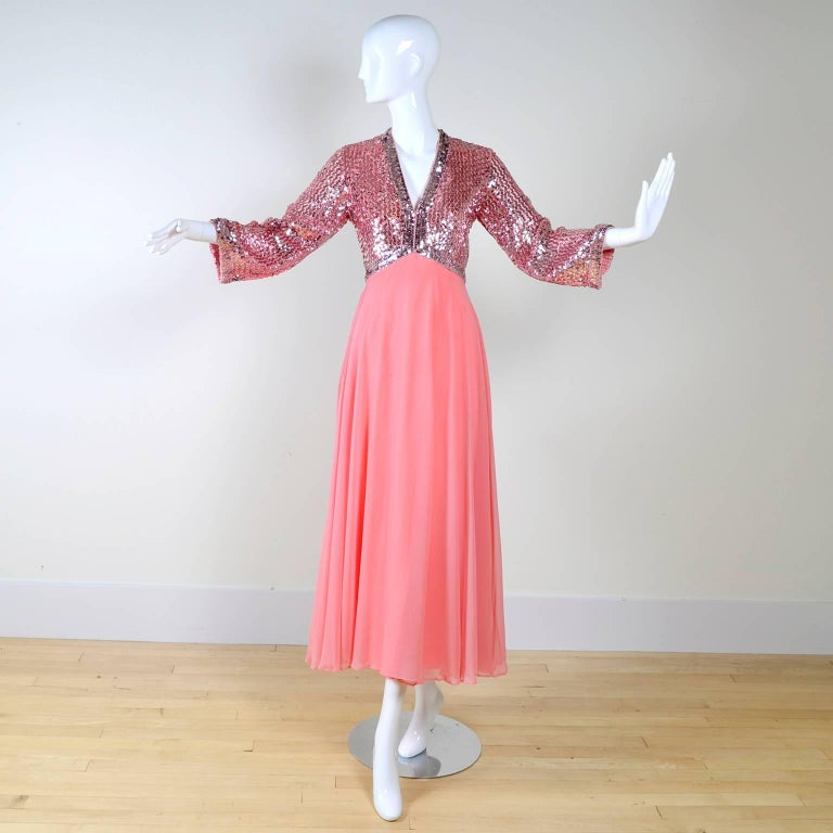 Gorgeous late 1960's or early 1970's pink dress with a lined chiffon skirt and deep V neck. The empire bodice is covered in silvery pink sequins, and is lined. This dress is in very good condition, with just a few loose threads. The arms are 3/4