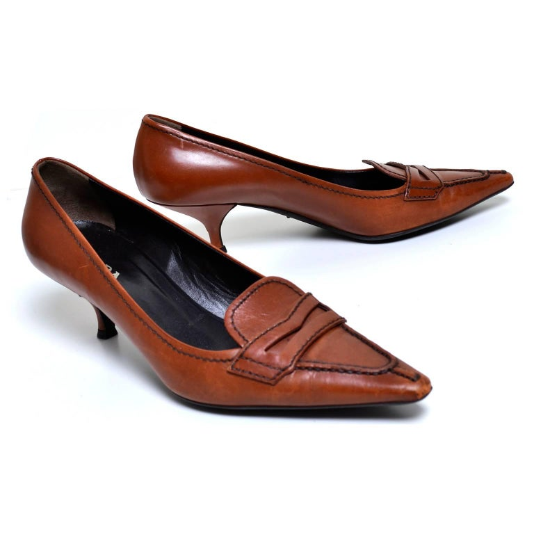 These are great vintage Prada loafers with a stylish pointed toe and perfect kitten heel. These loafers are a cognac brown, with dark brown stitching and a rubber sole. They are marked as a size 37 which is approximately a US women's size 6.5  and