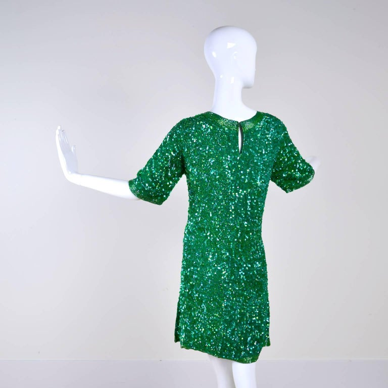 This pretty green sequin and beaded silk dress is a great dress to add to any wardrobe!  The dress has short sleeves and is lined with rayon. There is a back hook and eye at neck and there are beautiful rows of beading at the hem of the sleeves and