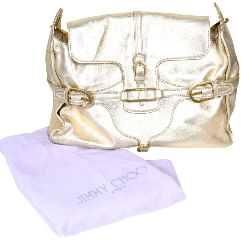"This is a great late 1990s or early 2000s Jimmy Choo gold metallic leather handbag with wonderful gold hardware.  The bag has 3 inside flap pockets, one zip pocket and its original dust bag. This bag measures 14"" across at the bottom, 10"" high and"